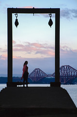 "the woman & the bridge, semi-silhouettes, evening at Dalgety Bay, looking towards the Forth Rail Bridge, Fife, Scotland. (grumpybaldprof) Tags: ""forthrailbridge"" cantilever railway bridge 1890 ""sirjohnfowler"" ""firthofforth"" woman colour evening summer water sea frame couds sky pastel pastelcolours silhouette semisilhouette ""dalgetybay"" dalgety fife scotland uk hdr canon 7d ""canon7d"" claire"