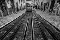 Along the Lines (DarrenCowley) Tags: alongthelines tram lisbon hill slope portugal monochrome blackandwhite lines urban streetphoto walls doors paving street darrencowley graffiti streetart