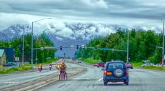 Oh No! (JLS Photography - Alaska) Tags: hdr alaska art artwork road intersection jlsphotographyalaska cars traffic tricycle biker mountains clouds digitalmanipulation digitalart