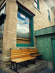 Rest Stop (AmyEAnderson) Tags: outdoors bench benches wisconsin boscobel southwestern grant county main street store building signs sign corrugated metal window reflection historic brick bricks green wooden platform corner vintage