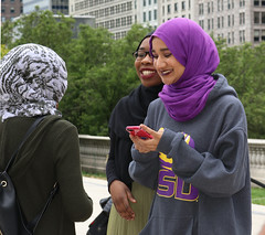 Street Portrait - Millennium Park - Downtown Chicago - 21 May 2017 - 80D (Andre's Street Photography) Tags: chicagoduplicatefile chicago downtown millenniumpark candid street straat straatportret straatfotografie streetportrait streetphotography fotografia distrada dastrada lacalle larue strasse color smiles muslin young women hijab traditionaldress lsu lousianastateuniversity lssweatshirt cell phone camera chicagoist chicagojournal chicagoreader chicagotribune chicagomagazine celebrate our common humanity ourcommonhumanity photobyandrevanvegten urban urbanphotography canon eos 80d eos80d efs1855stm outdoor fillflash happy laughing enjoyillinois illinois dedeka dutchstreetphotographer chicagostreetphotography chicagostreetphotographer tributetoedvanderelsken