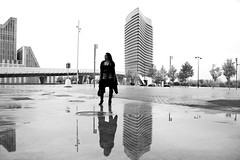 Urban reflections (Daniel Nebreda Lucea) Tags: woman mujer girl chica pretty guapa bella beautiful urban urbana city ciudad street calle architecture arquitectura building edificio construccion black white blanco negro floor suelo reflection reflejo water agua monochrome monocromo noir zaragoza europe europa fashion model canon 50mm 60d repetition repeticion structure estructura composition composicion people spain españa latin latina