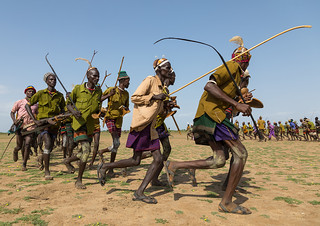Men running in line with weapons during the proud ox ceremony in the Dassanech tribe, Turkana County, Omorate, Ethiopia