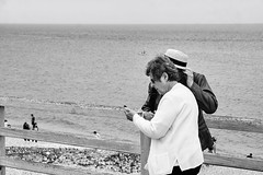 from the series: At the Beach (macplatti) Tags: france fra normandy etretat beach windy windig strand monochrome street streetphotography candidshot candid damen smartphone handy hut strohhut hat oldlady oldladies toruists touristen tourismus