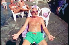 (Relax, Don't Do It) (Robbie McIntosh) Tags: leicamp leica mp rangefinder streetphotography 35mm film pellicola analog analogue negative leicam elmarit analogico leicaelmarit28mmf28iii elmarit28mmf28iii dyi selfdeveloped filmisnotdead autaut candid bellinifotoc41 beach tan seaside bathers strangers swimsuit colonnaspezzata man summer summertime sunglasses cinestill50d cinestill kodakvision3