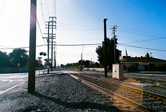 Railroad - L.A. (Pietro Bakke) Tags: yashica fx3 fx 3 35mm film films rullino rullini filmphotography photos photography photoshop lightroom lightmeter bakke7 pietro bacherotti trip holiday holidays vacation vacanze vacanza lavoro business travel california socal iso iso200 200 pose composizione composition los angeles sign zeiss 50mm f17 planar 28mm f28 28 17 50 mm lens analogic analogica 80s 1980 railway railroad rails treno passaggio livello streetphotography street road downey la high voltage highvoltage pylons