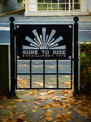 Sure to Rise (Steve Taylor (Photography)) Tags: suretorise established 1879 gate edmondsfactorygardens ferryroad leaves autumn path art architecture digital sign black brown green white grey metal road street tarmac newzealand nz southisland canterbury christchurch plant texture vigenette sunrise dawn