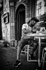 You're Not Around So I'll Eat Your Food (Alfred Grupstra) Tags: street streetphotography man eat door table