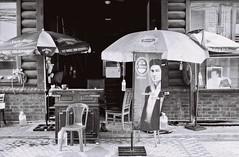 Shady (35mm) (jcbkk1956) Tags: umbrella thonglo film 35mm pan100 ilford manualfocus analog 167mt contax blackandwhite mono street thailand bangkok chairs posters advertising logos carlzeiss 45mmf28 worldtrekker