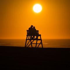 Sunrise Affection (Derek Boen) Tags: warmth love avalon newjersey jerseyshore beach shore ocean lifeguardchair sunrise sun