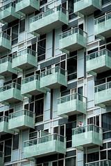 'One Among Many' (Canadapt) Tags: building balcony window man blue aquamarine graphic street toronto canadapt