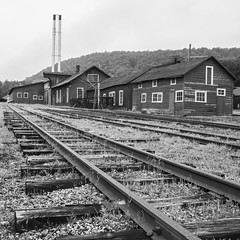 Old and Tired (trainmann1) Tags: nikon d90 amateur handheld summer june 2017 eastbroadtop eastbroadtoprailroad ebt rail railroad heritage historic antique relic abandoned neglected rusty crusty rust crust dirty orbisonia pa pennsylvania rockhill rockhillfurnace train trains bw blackwhite blackandwhite desaturated buildings exterior outside nikkor 18200mm track tracks rails ties ballast grass shops stacks wood metal steel iron rivets spikes weeds narrowgauge