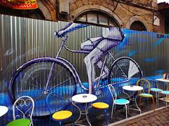 Ξανθη P1280414 (omirou56) Tags: ξανθη θρακη ελλαδα ελλασ γκραφιτι δρομοσ τραπεζακια καρεκλεσ χρωματα κτισμα ποδηλατο bike graffiti greece hellas street colors 43ratio panasoniclumixdmctz40 7dwf happbluemonday