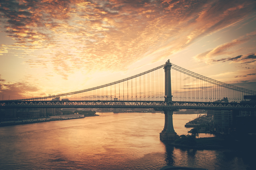 A sunrise shot of the Manhattan Bridge over the East River taken from the Brooklyn Bridge Pedestrian walkway.
