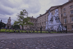 Trinity College Mural, Dublin (Colin Kavanagh) Tags: art streetart trinity thevolunteers joecaslin arteork cobblestone university history college dublin ireland visitireland visitdublin lovedublin architecture street clouds square mural bikes student