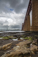 Location... location... location (andyrousephotography) Tags: forthrailbridge forthroadbridge queensferrycrossing bridges firthofforth southqueensferry jetty boat sand beach rocks bedrock seaweed lowtide foundations pillars seven 7 clouds stormy rain andyrouse canon eos 5d mkiii ef24105mmf4l