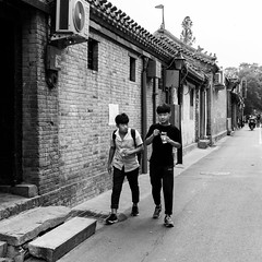 Cooling down (Go-tea 郭天) Tags: pékin beijingshi chine cn beijing gulou hutong history historical historic old ancient tradition traditional building house construction architecture narrow alley road hot wam day ice cream icecream 2 men young together team freinds cup spoon eat eating cool walk walking movement candid portrait street urban city outside outdoor people bw bnw black white blackwhite blackandwhite monochrome naturallight natural light asia asian china chinese canon eos 100d 24mm prime