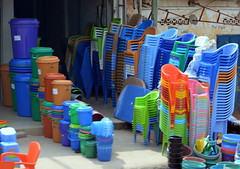 PLASTIC IN COLOR.  LOME, TOGO. (vermillion$baby) Tags: africa blue chair done flickr green lome market orange people street togo village colora seats