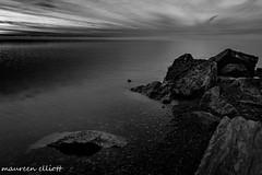 Dawn Awakening (maureen.elliott) Tags: blackandwhite 7dwf landscape water rocks shoreline dawn skies lakeerie greatlakes sunrise clouds earlymorning nature stillness