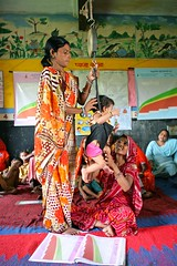 Accredited Social Health Activists (ASHA), Vimla Bai: 28 years old, monitoring weight of a child using MCP card...UNICEF India/2010/Giacomo Pirozzi....... (unicefindia) Tags: 1to5yearsold childcare grouppeople health india nutritionalgrowthmonitoring women