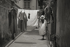 GuLangYu_girl with hat through laundry (Charles R. Yang) Tags: laundry streetphoto streetphotography china gulangyu xiamen island alley hat girl bw