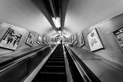 Escape Plan (Torsten Reimer) Tags: england escalator europa tunnel subway lights unitedkingdom underground london rolltreppe station advertisement tube embankment blackandwhite schwarzweis europe uk ubahn gb