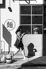 A Woman under the long shadow in front of the Chinese Noodle Shore, Wan Chai, Hong Kong (Job Homeless) Tags: people portrait blackandwhite bw streetsnap streetphotography leica canon50mmf095 monochorme monotone m8