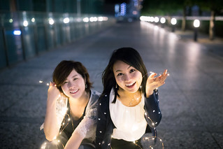 Happy young business women playing with lights after work