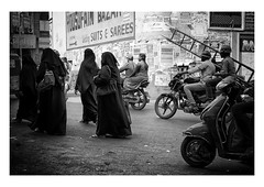 follow that sign (handheld-films) Tags: india streets city cities hyderabad people activity muslim islam hindu women niqab burka burqa blackandwhite monochrome ladder bikes group advertisement sign travel indian subcontinent busy bustling