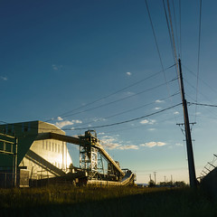 Leave You When the Summer Comes (rosenunezsmith) Tags: lanecounty corrugatedbuilding eugene telephonelines oregon sunset grass lumbermill industrial goldenhour sky builtlandscape pacificnorthwest telephonepoles america powerlines pnw upperleftusa magichour