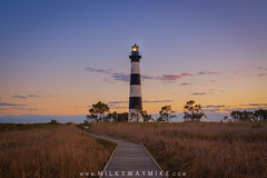 Bodie Island Lighthouse Sunset (Mike Ver Sprill - Milky Way Mike) Tags: sunset sunrise boardwalk board walk path pathway walkway way tall wheat grass wetlands marsh bodie island lighthouse light house colorful vibrant nags head national park seashore east coast north carolina surreal serene peaceful gorgeous beautiful landscape mike ver spprill sky