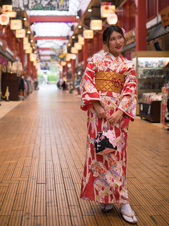 Young woman in kimono standing in traditional Japanese shopping mall