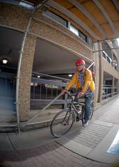 Yellow Jacket (Kurayba) Tags: edmonton alberta canada ca fisheye takumar 18mm f11 downtown pentax k1 full frame ff mode pancake prime lens cyclist man cycling bicycle street yellow jacket