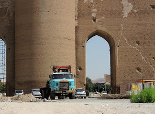 Turquoise truck by large ancient brick gate of Tabriz, Iran