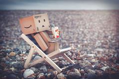 Deckchair Danbo. (Matt_Briston) Tags: danbo robot deckchair deck chair pebbles beach cley next sea matt cooper nikon d90