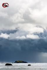 Oregon Island (KnightedAirs) Tags: bandon beach oregon d5200 nikon nikkor 35mm digital afs ocean stone rock formation monolith sand sky clouds landscape nature coast coastal blue warm sun storm island green