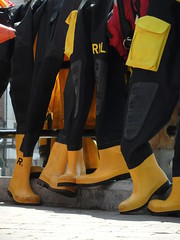 Leaning on a lifeboat (Nekoglyph) Tags: whitby yorkshire rnli wellies rubber boots black orange yellow lifeboats shadows fence draped wetsuits drying