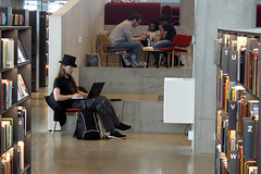 A hipster at the library (Ib Aarmo) Tags: dokk1 århus public library hipster top hat reading working computer shelves books