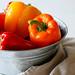 Rote und gelbe Paprika in Metallschale
