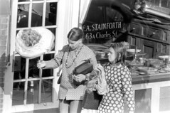 h21-68 21 (ndpa / s. lundeen, archivist) Tags: nick dewolf nickdewolf bw blackwhite photographbynickdewolf film monochrome blackandwhite city summer 1968 1960s 35mm boston massachusetts candid streetphotography citylife streetlife people beaconhill charlesstreet sidewalk pedestrian youngpeople pedestrians shop store business storefront window storewindow windowdisplay antiques antiqueshop bostonantiqueshop thebostonantiqueshop fastainforth stainforth 63acharlesstreet door woman women youngwoman youngwomen black africanamerican paperflower glasses eyeglasses clothes clothing fashion necklace antiquesstore antiquesshop bostonantiquesshop thebostonantiquesshop antiquestore