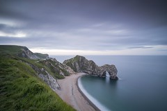 Durdle Door (silvcurl009) Tags: landscape water sand markers calm blue beach bay boats beachhuts clouds coastal coast coastline crag cliff cove dawn daylight dorset daybreak durdledoor exposure seascape sea red formations flowers fence grass green jurassic sky rocks rockformations light longexposure land long life movement morning national outdoor ocean orange outdoors old pebbles tide view remains rock rocksky sun sunshine shore sunset serene sunrise seaside summer scene structure surf steps serenity thrift trees wave white waterfront