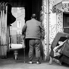 Back in pain (Go-tea 郭天) Tags: qingdao old man stick wood wodden chair small foldable day sunny sun shadow home building walk walking pain difficulty difficult back backside gate door open opened through go going cross crossing movement slow canon eos 100d 50mm prime street urban city outside outdoor people bw bnw black white blackwhite blackandwhite monochrome naturallight natural light asia asian china chinese shandong alone lonely grandpa