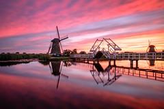 Fired sky Kinderdijk (Mario Visser) Tags: kinderdijk sunset firedsky color red windmill bridge unesco water reflection fujifilm