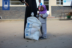 A small girl with Islamic Relief USA's food parcel in Zimbabwe.