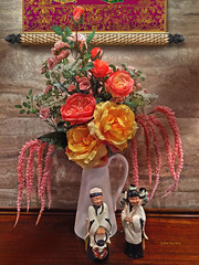 Floral w/ Figurines (John Jardin) Tags: figurines objects flowers floral arrangement colorful colors california stilllife statue shadows vase yellow orange pink coral stone vintage asian roses scroll art wall exotic interior dramatic decor light wood