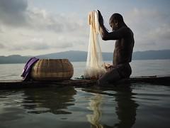 Fisherman, Lake Bosumtwi, Ghana ([The World Through My Eyes]) Tags: lake lago sacred sagrado gana ghana fisherman pescador water reflection