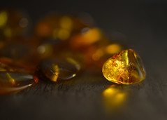 amber bracelet for macro mondays 'broken' (Emma Varley) Tags: amber bracelet light glow reflection orange lowkey jewellery broken wood bokeh