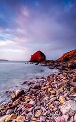 Red rock (emmadavidso) Tags: sunrise marloes pembrokeshirelandscape pink pebbles blue clouds longexposure