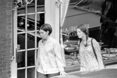 h27-68 20 (ndpa / s. lundeen, archivist) Tags: nick dewolf nickdewolf bw blackwhite photographbynickdewolf film monochrome blackandwhite city summer 1968 1960s 35mm boston massachusetts candid streetphotography citylife streetlife people beaconhill charlesstreet sidewalk pedestrian youngpeople pedestrians door store shop business storefront stainforth fastainforth 63acharlesstreet antiqueshop bostonantiqueshop thebostonantiqueshop antiques plates candlesticks window storewindow windowdisplay woman youngwoman women youngwomen brunette longhair pigtails braid braided purse shoulderbag car vehicle automobile parkedcar antiquesstore antiquesshop bostonantiquesshop thebostonantiquesshop antiquestore
