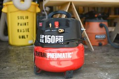 harbor freight's red/black air compressor in a wood shop